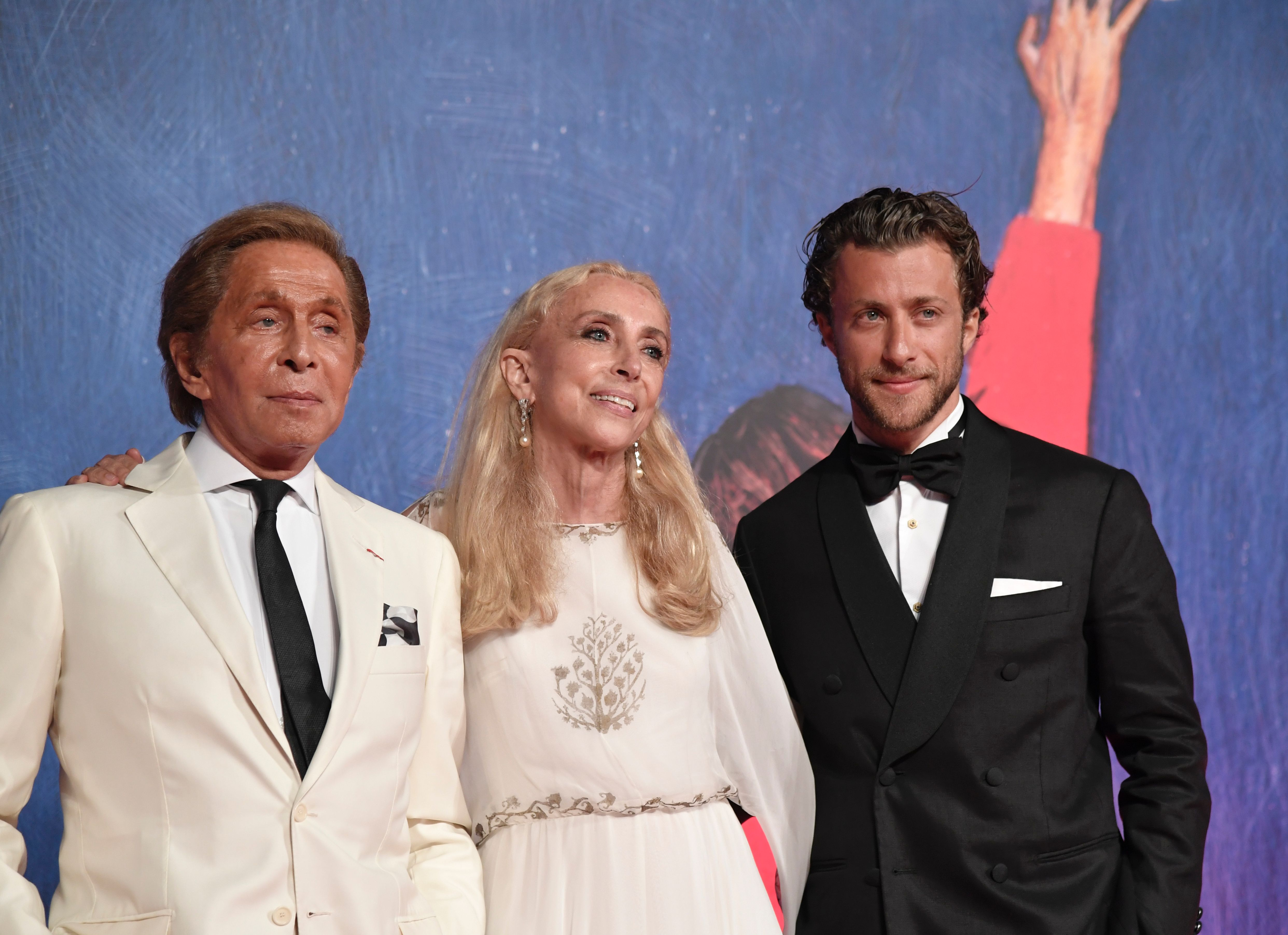 "Italian designer Valentino (L) arrives with director Francesco Carrozzini and fashion editor Franca Sozzani for the premiere of the movie ""Franca : Chaos and Creation"" presented out of competition at the 73rd Venice Film Festival on September 2, 2016 at Venice Lido. / AFP PHOTO / TIZIANA FABI"